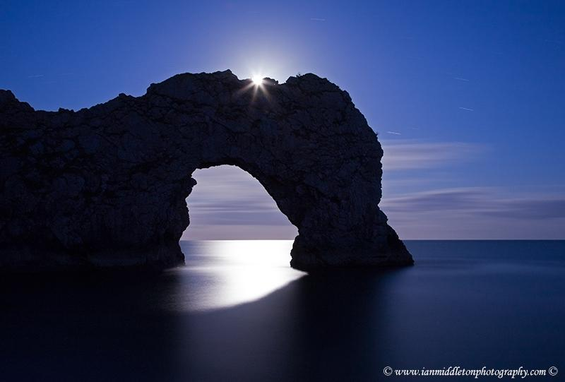 Moon rising at dusk over the rock arch at Durdle Door on the stunning Jurassic Coast in Dorset England & Moon over Durdle Door | Shutterbug